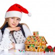Girl in Santa's hat with gingerbread house — Stock fotografie
