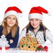 Girls in Santa's hat with gingerbread house — Foto de Stock