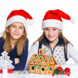 Girls in Santa's hat with gingerbread house — Stok fotoğraf