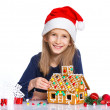 Girl in Santa's hat with gingerbread house — Stok fotoğraf