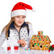 Girl in Santa's hat with gingerbread house — 图库照片