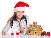 Girl in Santa's hat with gingerbread house — Stock Photo