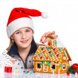 Girl in Santa's hat with gingerbread house — Foto Stock