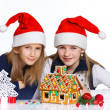 Girls in Santa's hat with gingerbread house — ストック写真