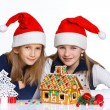 Girls in Santa's hat with gingerbread house — Photo