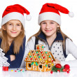Girls in Santa's hat with gingerbread house — Stock fotografie