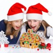 Girls in Santa's hat with gingerbread house — Stockfoto