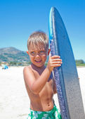 Boy has fun with the surfboard — Stockfoto