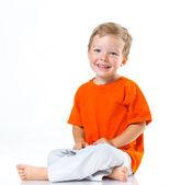Happy boy sitting on the floor — Stock Photo