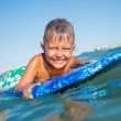 Boy has fun with the surfboard — Stock Photo #37857617