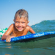 Boy has fun with the surfboard — Stock Photo #38081343
