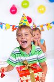 Jongen met geschenkdoos op verjaardagsfeestje — Stockfoto