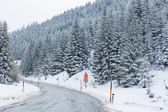 Road through snowy mountains — Stockfoto