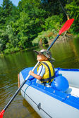 Happy little boy paddling kayak — Stock Photo
