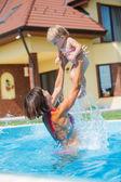 Familia jugando en la piscina. — Foto de Stock
