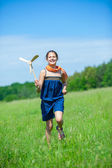 Girl in summer day holds windmill — Photo