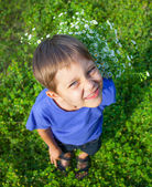 Boy with wild spring flowers — Stock Photo