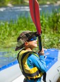 Happy young boy holding paddle near a kayak — Stock Photo