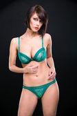 Young woman in elegant green lacy underwear — Stock Photo
