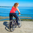 Beautiful woman with bicycle at the sea — Stock Photo