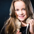 Girl with fair long hair in fur vest on dark background — Stock Photo #14704275
