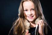 Meisje met eerlijke lange haren in bont vest op donkere achtergrond — Stockfoto