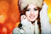 Beautiful girl with winter fur cap on bright background — Stock Photo