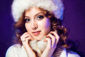 Beautiful girl with winter fur cap on purple — Stock Photo