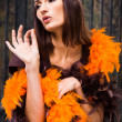Actress in brown and orange boa — Stockfoto