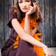 Smoking actress in brown and orange boa — Stock Photo