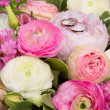 Wedding rings on bouquet of white and pink peonies — Stock Photo #22309519