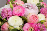 Wedding rings on bouquet of white and pink peonies — Stock Photo