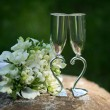 Two wedding glasses and bridal bouquet in summer garden — Stock Photo #22605921