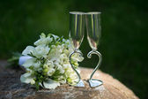 Two wedding glasses and bridal bouquet in summer garden — Stock Photo