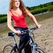 Beautiful woman with bicycle at the sea — Stock fotografie
