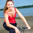 Beautiful woman with bicycle at the sea - Stock Photo
