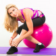 Beautiful woman fitness instructor sitting on stability ball — Stock Photo