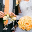 Hands of bride and groom holding wedding bouquet and glasses — Stock Photo #40583949