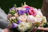 Hands of bride and groom holding wedding bouquet — Stock fotografie