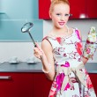 Blond girl ready for cooking in interior of red modern kitchen — Stock Photo #5975696