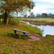 Wooden table and benches by river — Stock Photo