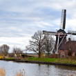 Stock Photo: Dutch windmill by canal