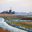 Dutch windmill by river in winter - Stock Photo