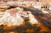Stones in acidic rio Tinto — Stock Photo