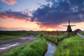 Warm sunrise over Dutch windmill and river — Stock Photo