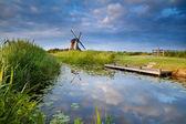 Molino de viento y azul cielo reflejado en el pequeño lago — Foto de Stock