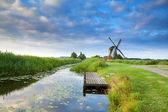 Molino de viento holandés por el río con cielo azul reflejada — Foto de Stock