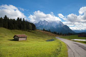 Caseta de madera en prado y altos alpes bávaros — Foto de Stock