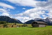 Greem çayırlar üzerinde mavi gökyüzü üzerinde birkaç kulübeleri — Stok fotoğraf