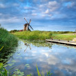 Blue sky and windmill reflected in river — Stock Photo